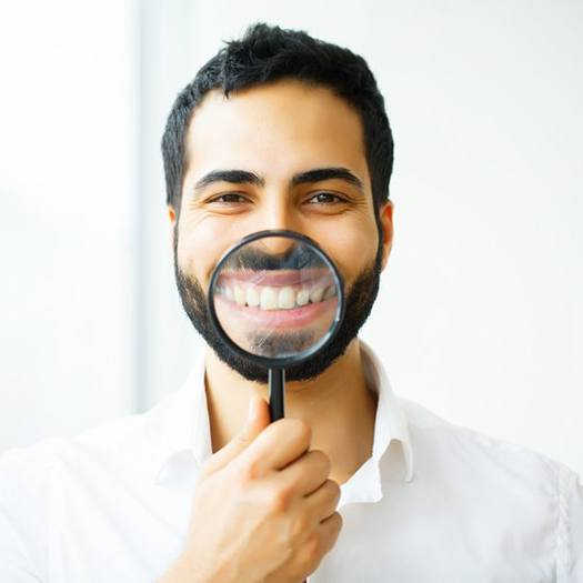 man holding magnifying glass to showcase his smile with dental crowns in Summerfield