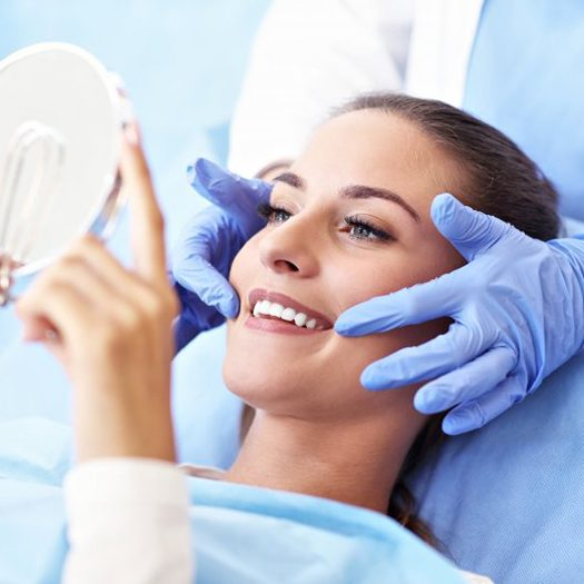 young woman admiring results of her dental treatment in hand mirror