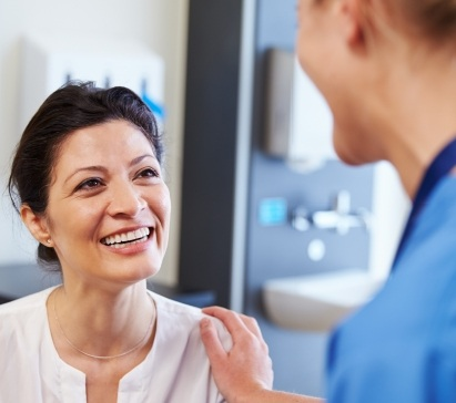 Smiling woman talking to dentist about dental treatment plan