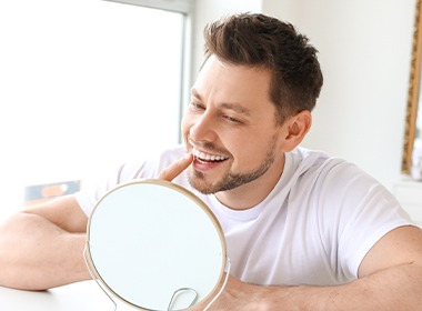 Man pointing to smile and looking in a mirror